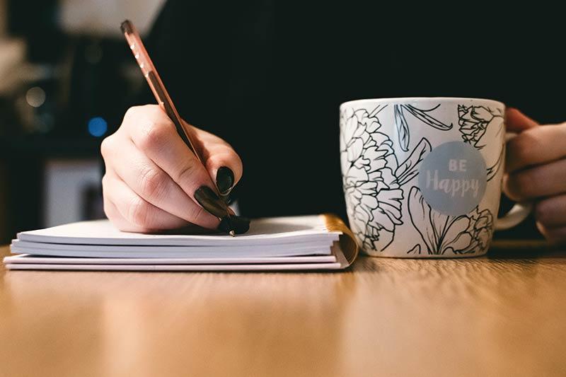 Een dame die met een blocknote en een kop koffie aan de slag is met haar content strategie opzetten.