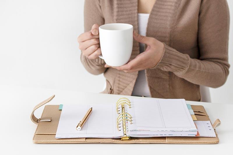 Dame met mok in haar hand en notitieboek voor zich.